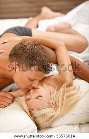 Intimate couple during sexual intercourse on the bed - stock photo