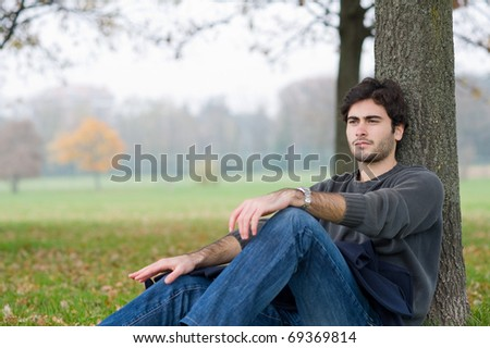 Intimate portrait of man outside in a park. - stock photo