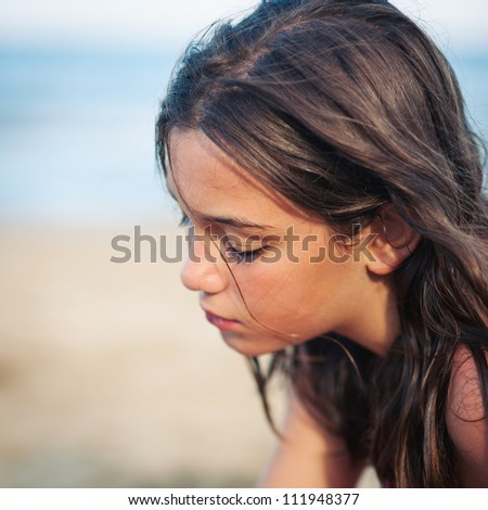 Intimate portrait of young girl on the beach. Shallow depth of field. - stock photo