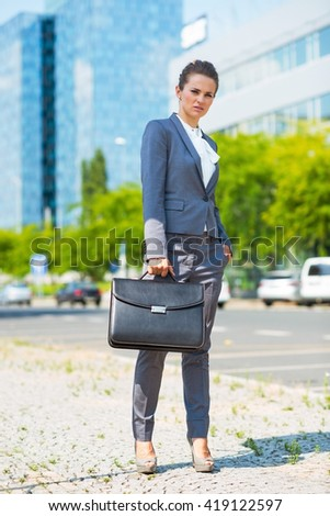 Into the ultra-modern business trends. Full length portrait of business woman with briefcase in modern office district - stock photo