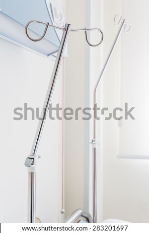 Intravenous pole stand for serum, blood, pharmaceutical bags in brightly lit hospital room over a bed at treatment end. Natural sunlight gives a positive feeling of patient's successful full recovery. - stock photo