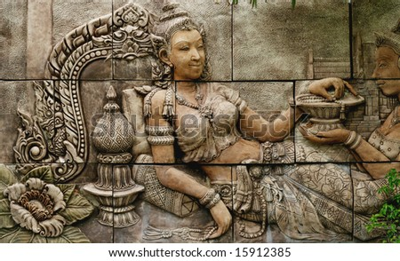 Intricate Thai carving mural - travel and tourism. - stock photo