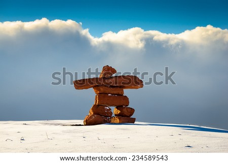 Inukshuk in the snow against the clouds. - stock photo
