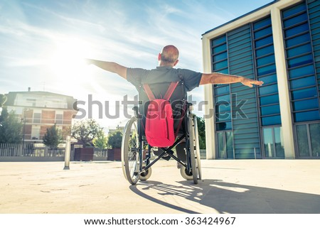 Invalid man sitting on a wheel chair and enjoying a walk outdoors - stock photo