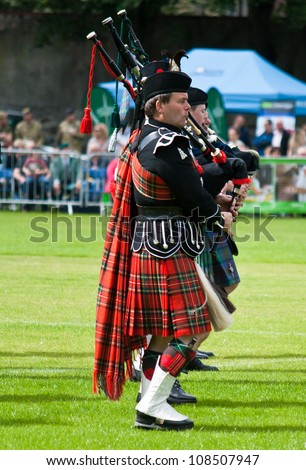 INVERNESS, SCOTLAND - JULY 21: An unidentified member of The Royal British Legion Pipe Band takes part in the annual Inverness Highland Games in Inverness, Scotland on July 21, 2012. - stock photo