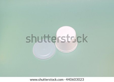 inverted plastic container with a lid Hot food and drinks on a green background - stock photo