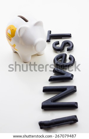 Invest money concept.White piggy bank with Invest inscription on a white table.Investment,Protection money. - stock photo