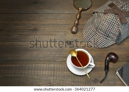 Investigation Concept. Private Detective Tools On The Wood Table Background. Deerstalker Cap,  Magnifier, Key, Cup, Notebook, Smoking Pipe.Overhead View - stock photo
