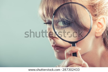 Investigation exploration education concept. Closeup funny woman face, girl holding on eye magnifying glass loupe - stock photo