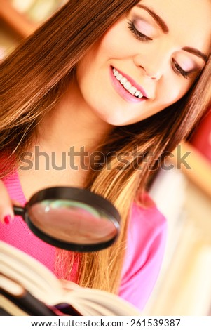 Investigation exploration education concept. Closeup intelligent student girl in library, woman holding magnifying glass loupe - stock photo