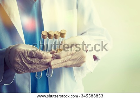 Investigator checking test tubes - stock photo