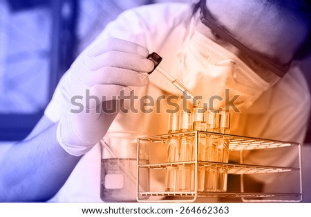 Investigator checking test tubes. Man wears protective goggles - stock photo