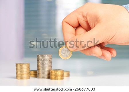 Investing concept. Hand putting euro coin on stack of coins - stock photo