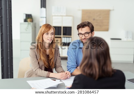 Investment broker meeting with a young couple in her office to discuss their financial needs, view from behind the agent of the couple - stock photo