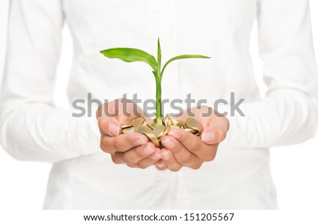 Investment concept, close up of female hands holding stack of golden coins with small plant growing out of it - stock photo