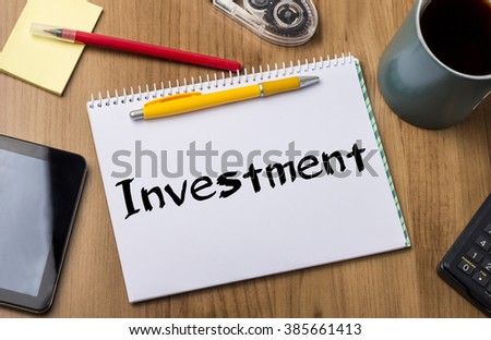 Investment - Note Pad With Text On Wooden Table - with office  tools - stock photo