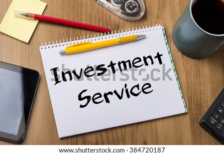 Investment Service - Note Pad With Text On Wooden Table - with office  tools - stock photo
