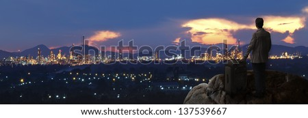 investor with big bag standing on the rock and looking to industry city use for people and investment topic - stock photo