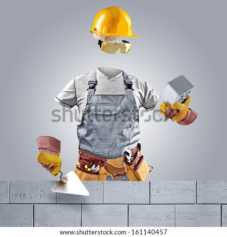 invisible worker with trowel and brick wall - stock photo