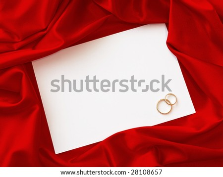 invitation card with two wedding rings and red cloth around - stock photo