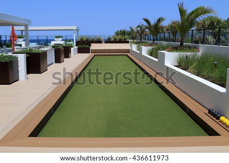 Inviting bocce ball court with artificial turf on a rooftop terrace. - stock photo