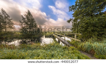 Inviting Footbridge  crossing river on a windy summer morning with breaking clouds in september near Eelde, Drenthe, Netherlands - stock photo