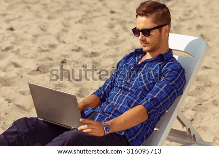 Involved in work. Positive handsome freelancer  sitting on the beach and holding notebook while working. - stock photo
