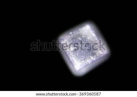 Iodized table salt crystals photographed through a Microscope at 10x their normal size. Photo taken with a DSLR through a Microscope. Lighting from above. unfocused  - stock photo