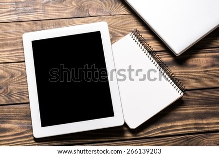 Ipad. Digital tablet computer with note paper and cup of coffee on old wooden desk. Simple workspace or coffee break with web surfing. - stock photo