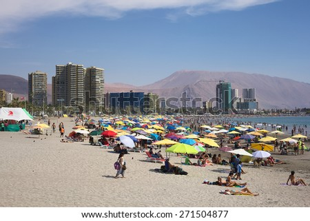 IQUIQUE, CHILE - JANUARY 23, 2015: Unidentified people enjoying the summer on the crowded Cavancha beach on January 23, 2015 in Iquique, Chile. Iquique is a popular beach town in Northern Chile.   - stock photo