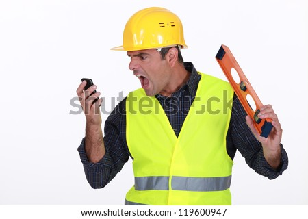 Irate builder shouting down phone - stock photo