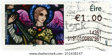 IRELAND - CIRCA 2014: An Post Christmas stamp printed in Ireland show angel with lute at Millstreet Parish Church in Co Cork; adoration of Magi; stained glass window by Harry Clarke; �1.00; circa 2014 - stock photo