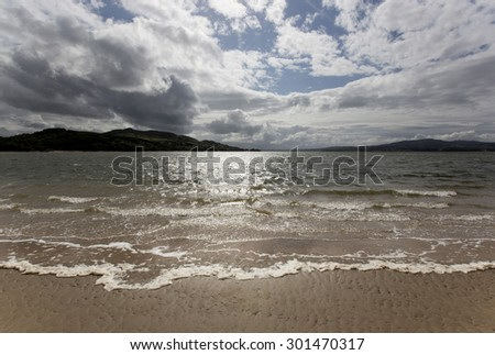Ireland west coast landscape scene during stormy weather in summer on a sandy beach with small waves breaking and sun shining through broken cloud. - stock photo