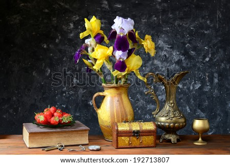 Irises in a ceramic vase and fresh strawberries on table - stock photo