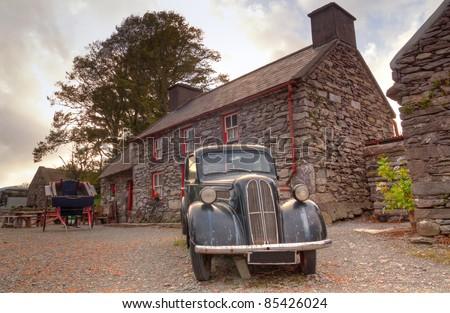 Irish cottage house with old car - stock photo
