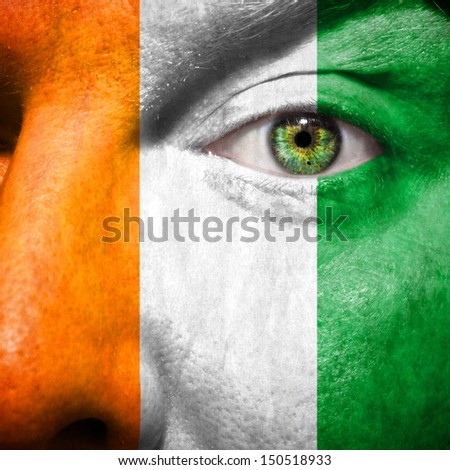 Irish flag painted on mans face to support his country Ireland - stock photo