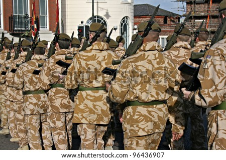 Irish Guards returning home from war, rear view - stock photo