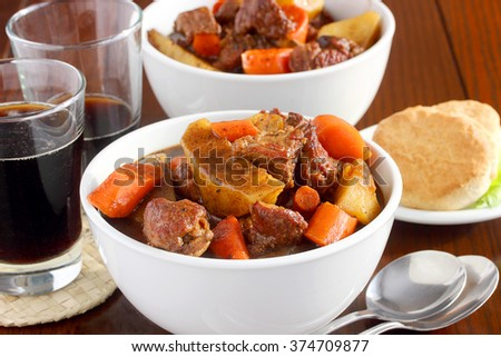 Irish lamb stew served with dark beer and soda biscuits is a traditional meal for St. Patrick's Day - stock photo