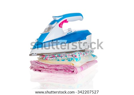 Iron and  pile of clothes on white background - stock photo