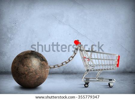 Iron ball with empty shopping cart, closeup - stock photo