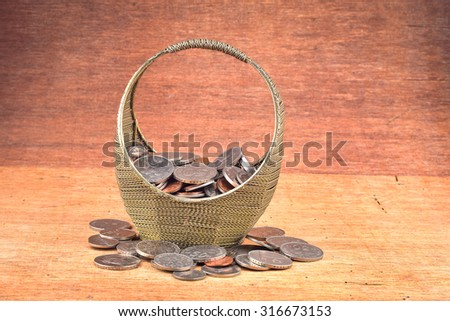 Iron basket full of coin on wooden background - stock photo