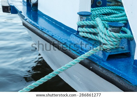 Iron Berth Holding White Boat Lines on a White and Blue Boat Near Shore - stock photo