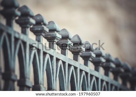 iron cross, fence with decorative metal flourishes - stock photo