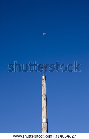 Iron cross on the Camino de Santiago / Way of Saint James with the clear sky and the Moon - stock photo