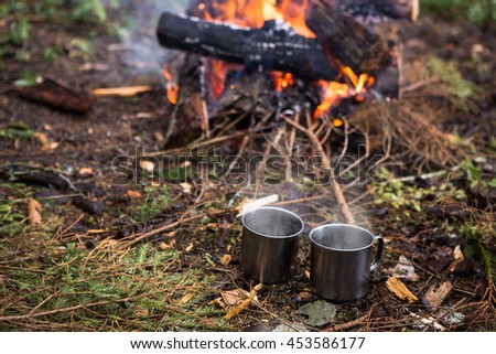 Iron cup with tea, fire, forest, - stock photo