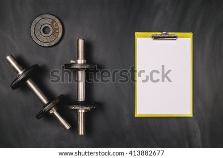 Iron dumbbells on a black chalkboard seen from above. Photo taken from above, top view. Conceptual image background for sport or fitness advertising. Horizontal image. - stock photo