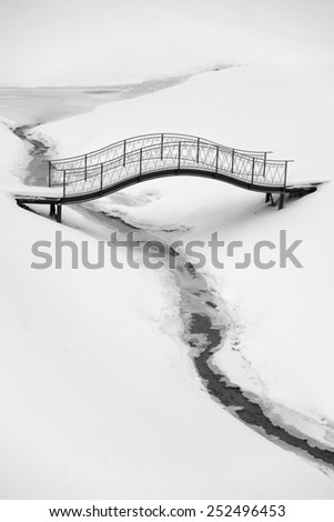 Iron footbridge over winter creek - stock photo