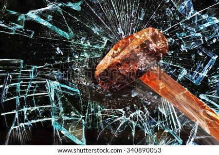 Iron hammer breaking glass window. - stock photo