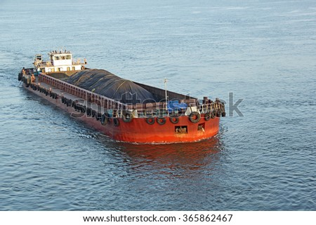 Iron ore mined in hinterland transported to the main harbor in large cargo boat for loading into big ships for exporting in India - stock photo