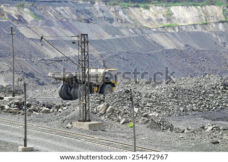 Iron ore opencast mining site: dump truck driving along the road - stock photo